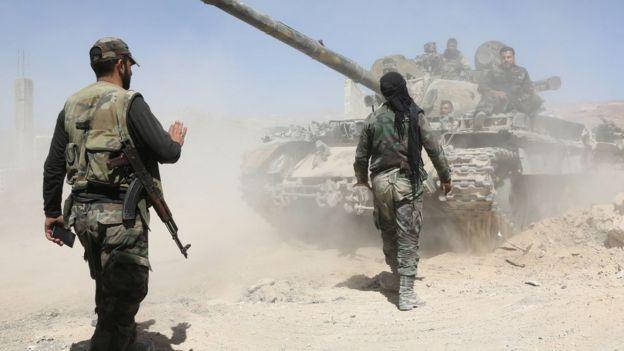 Dos soldados de las fuerzas gubernamentales sirias caminando hacia un tanque.