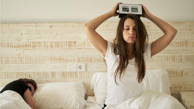 Mujer con cara de agobio despertándose a las 7 de la mañana