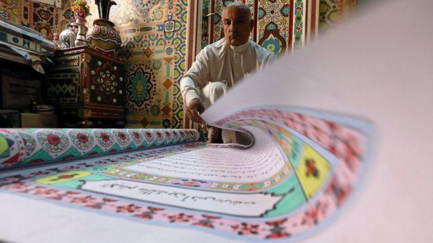 سعد محمد يقلب صفحات نسخة أخرى من المصحف كتبها بخط يده