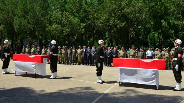 Turkish soldiers, army officers and officials stand at attention next to the coffins of soldiers Mehmet Kocak and Ismail Yavuz, during a ceremony in Diyarbakir, Turkey (26 July 2015)