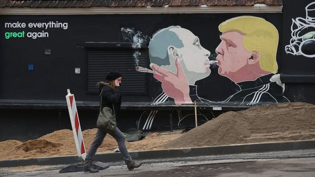 A woman walks past a mural of Donald Trump (R) blowing marijuana smoke into the mouth of Vladimir Putin in Vilnius, Lithuania