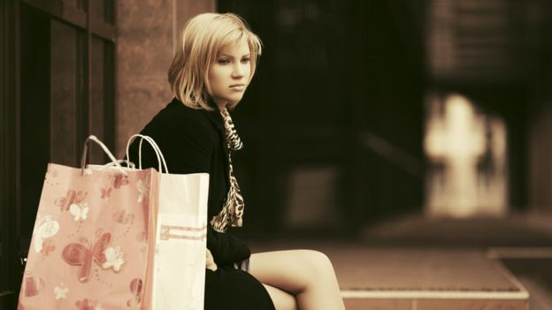 A woman with shopping bags and sad expression