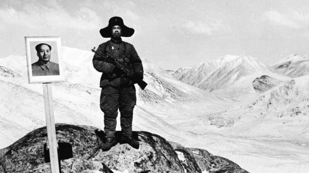 Um guarda de fronteira com um retrato de Mao Tsé Tung