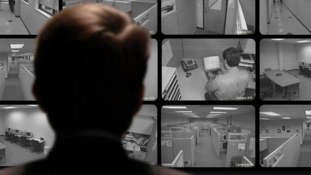 Un hombre mira varios monitores de una oficina