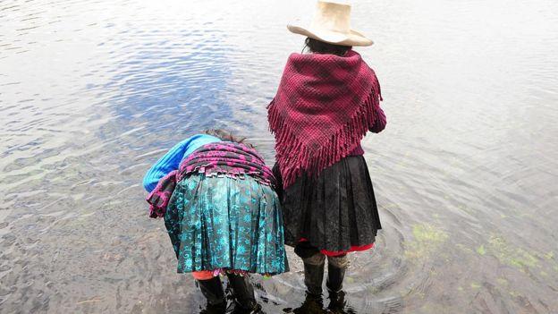 Dos indígenas en un lago