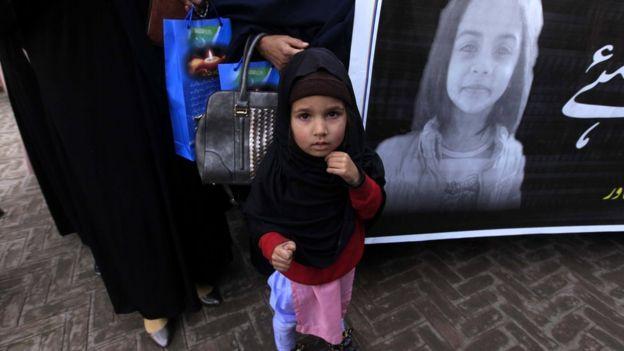 девочка на фоне плаката с фото Зейнаб