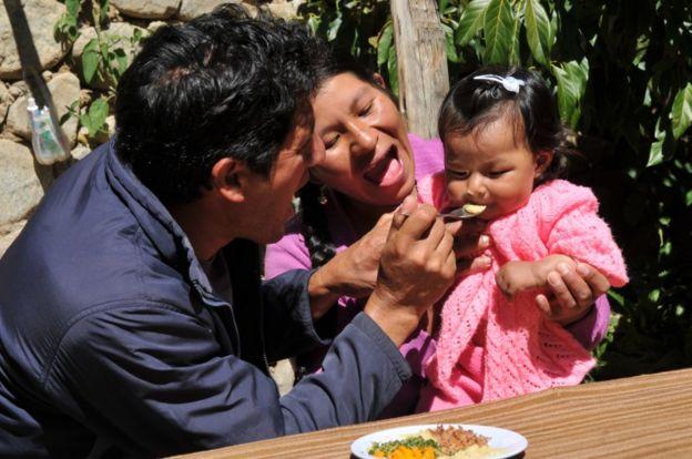 Padres alimentando a hija en Perú.