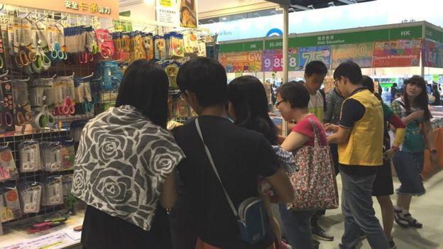 游客在书展选购特价文具。