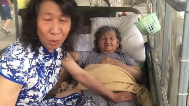 Still from the video showing the man with his mother while dressed in a traditional Chinese dress and with long hair