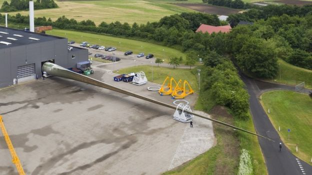 Aerial shot of prototype turbine blade emerging from factory