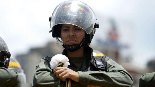 Una funcionaria de la GNB con una flor blanca que le entregó una manifestante de la oposición.