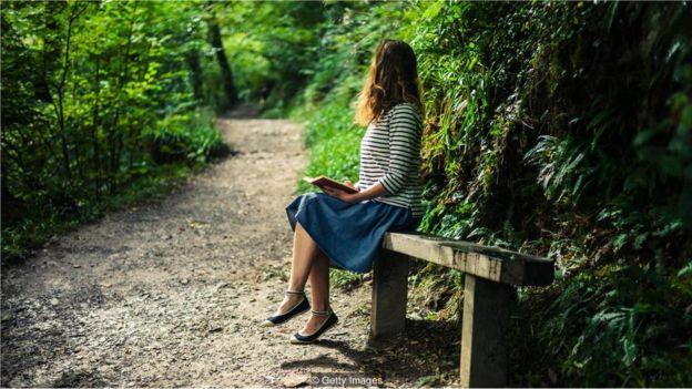 Mulher lê livro em banco de parque