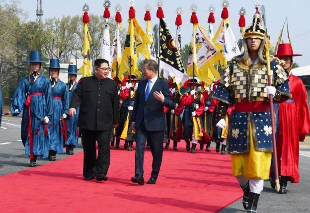 Kim Jong-un y Moon Jae-in caminan y hablan.