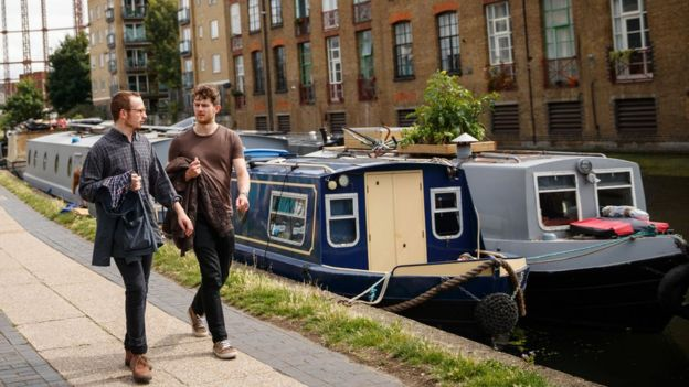 Two men walk by a canal in East London