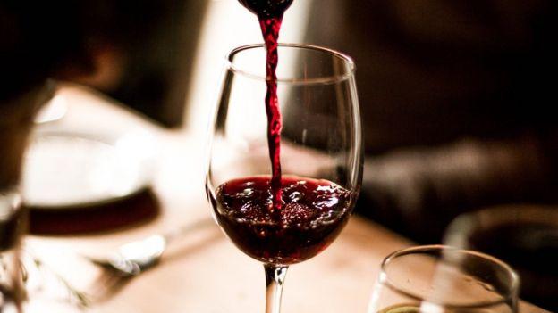 В бокал наливается красное вино