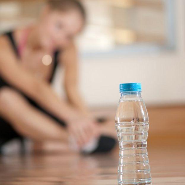 Una botella de agua delante de una mujer haciendo ejercicios