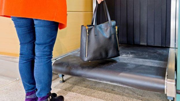 Imagen ilustrativa de una mujer ingresando un bolso persona en una m??quina de rayos X de control de seguridad.