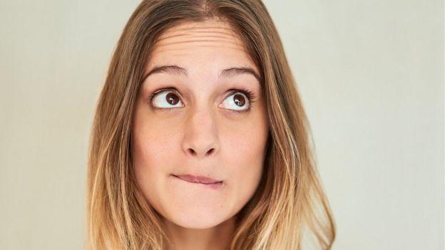 una mujer joven se muerde los labios