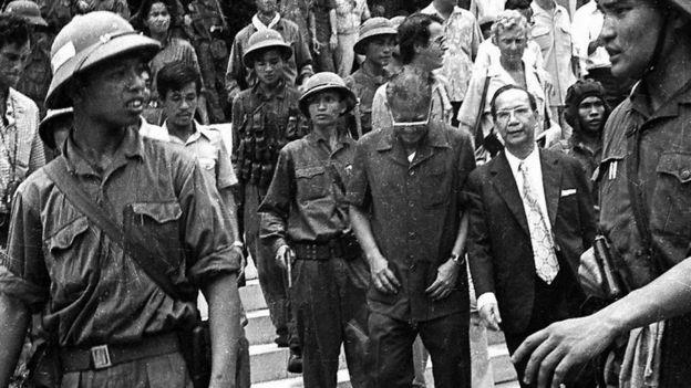 Tổng thống Dương Văn Minh (đeo kính, cúi đầu) bị bộ đội cộng sản đưa đi. (Bản quyền hình ảnh GETTY IMAGES)