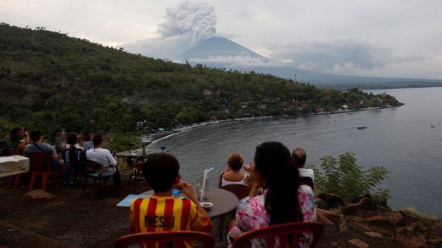旅客從艾眉灣附近的咖啡廳眺望冒著濃煙的火山。
