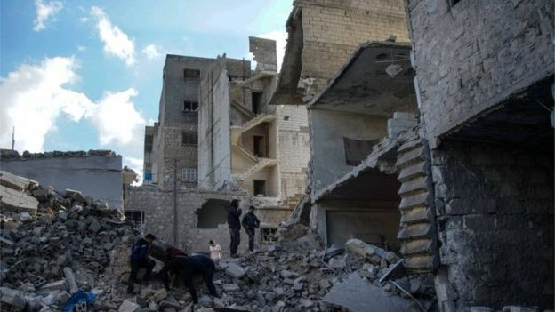 People inspect the rubble at a market center in the town of Areeha, after an air strike
