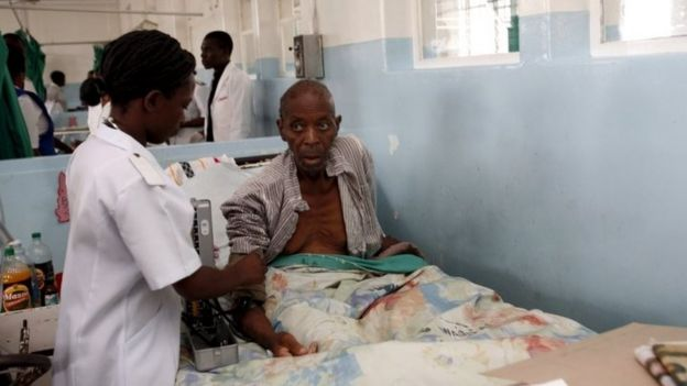 An elderly patient receives treatment from a nurse while sitting up in bed at Harare central hospital (28 February 2009)