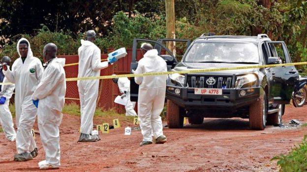 Ugandan police in white protective suits at a murder scene
