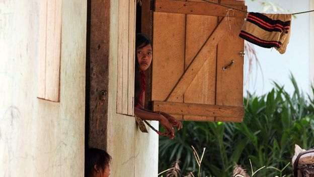 A girl looking out of the window on the Orang Rimba estate