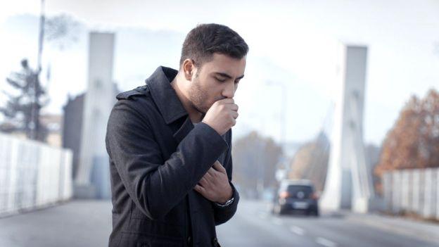 Hombre tosiendo en la calle.