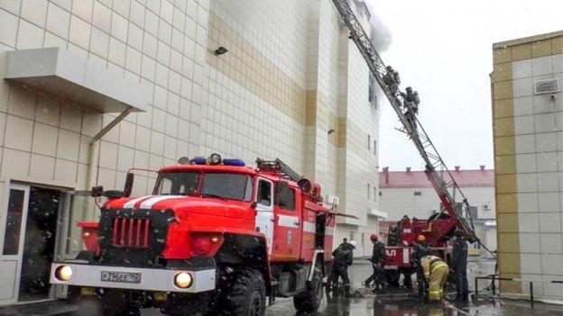 Bomberos suben escaleras para alcanzar el incendio