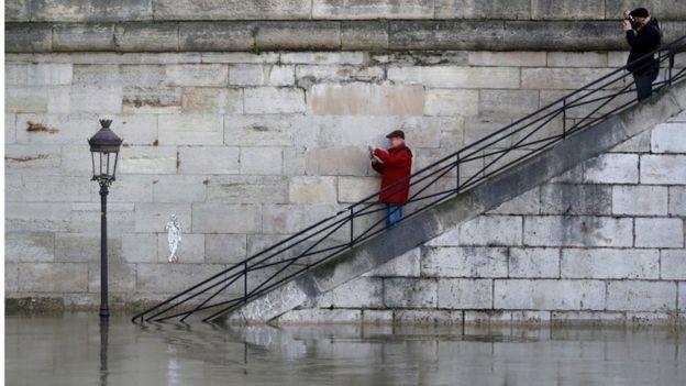 Two men on steps photograph flooding River Seine, Paris, 26 Jan 2018