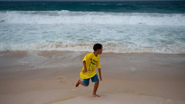 Boy from a favela during a demonstration demanding for peace in Copacabana beach