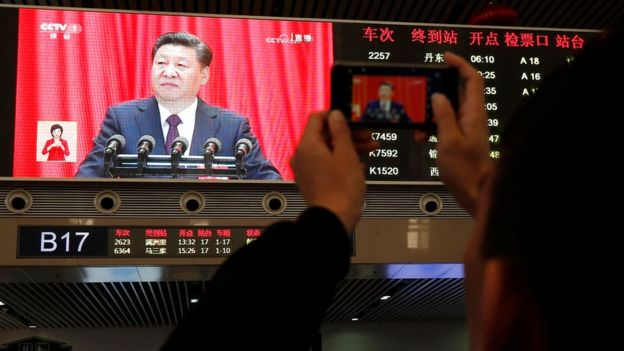 A passenger takes pictures of Chinese President Xi Jinping at Shenyang railway station in China