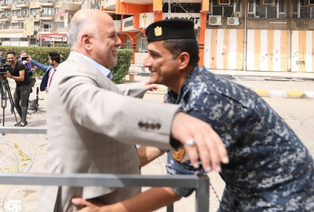 Prime Minister Haider al-Abadi is searched before entering a polling station in Baghdad, 12 May 2018