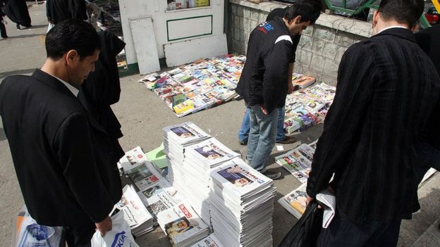 Iranian men look at stacks of newspapers in Tehran (file)