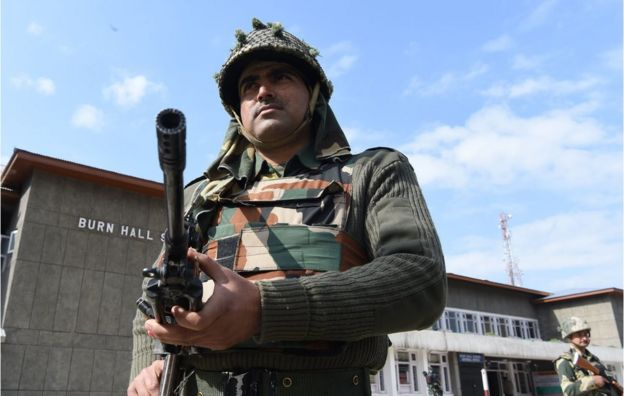 Indian paramilitary soldiers stand guard at a polling station in Srinagar on 9 April 2017.