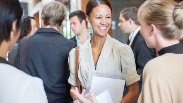Una joven sonriendo entre un grupo de gente