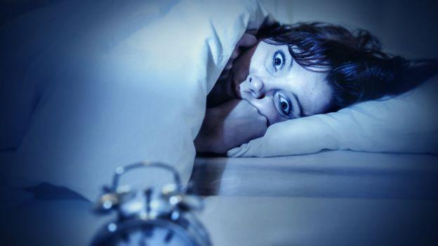 Mujer en la cama con ojos abiertos.
