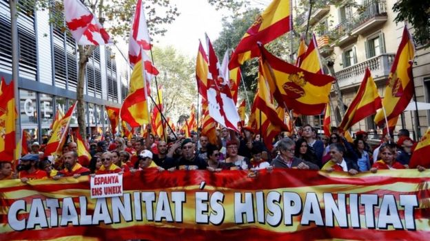 Demonstrators march with a 'Catalanitat es hispanitat' sign