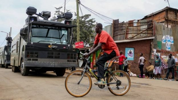 A man cycles past riot police water canons patrolling ahead of the Presidential election in Kibera slums of Nairobi, Kenya, 7 August 2017
