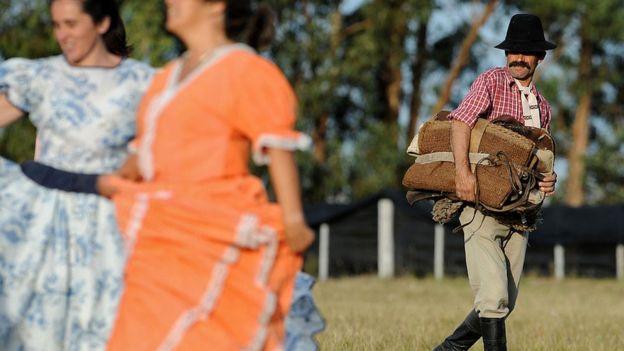 Un hombre de campo uruguayo mira a dos mujeres bailar.
