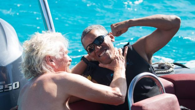 Former US President Barack Obama and British businessman Richard Branson sit on a boat in the British Virgin Islands