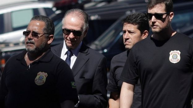ブラジルのオリンピック委員会の大統領は、スーツとサングラスを着て、連邦役員の間に描いた