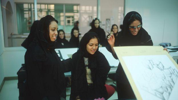 Jóvenes estudiantes en Arabia Saudita con túnicas y el pelo cubierto