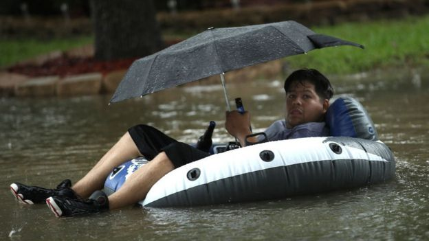 Un hombre bajo un paraguas y a bordo de una lancha huye en una calle inundada de Houston.