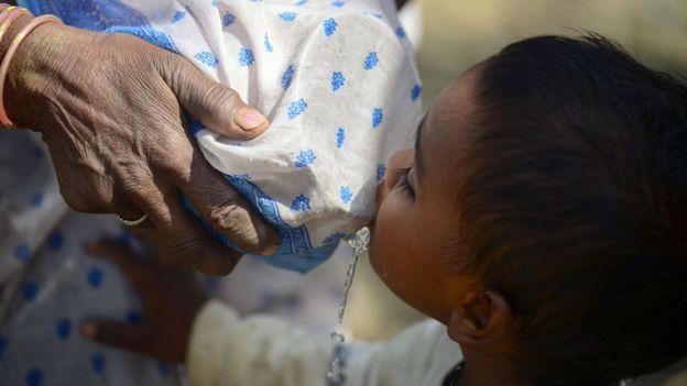Niño tomando agua de un recipiente en el que un adulto colocó una tela para filtrar el líquido