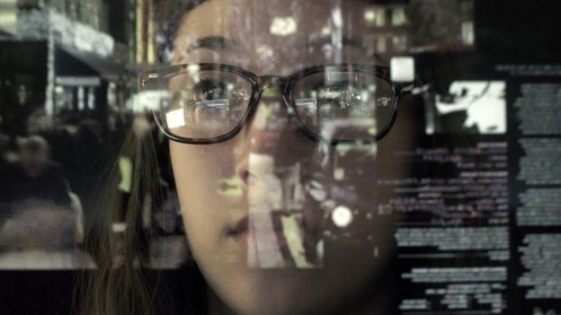 Mujer con gafas y reflejo en cristal.