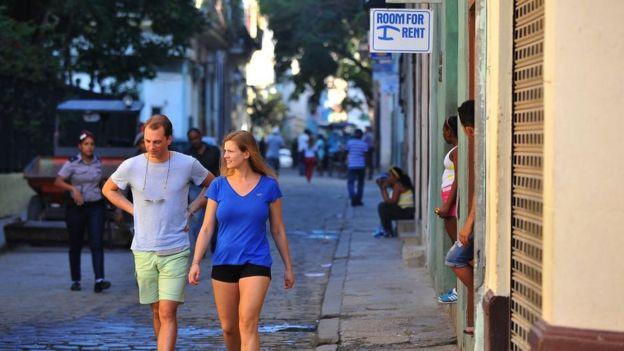 Turistas caminan cerca de una casa que alquila habitaciones para turistas.