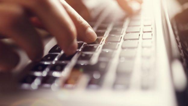 Mãos sobre teclado de computador