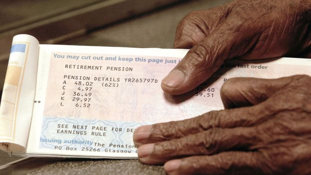 An elderly man holding a pension book